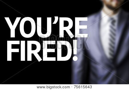 You're Fired! written on a board with a business man on background