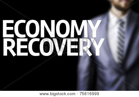 Economy Recovery written on a board with a business man on background