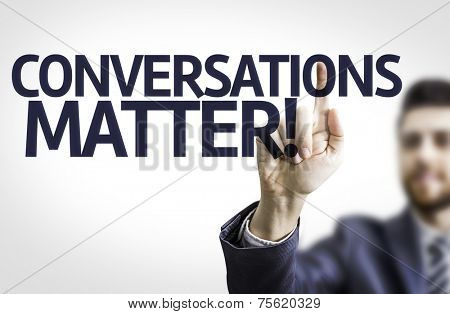 Business man pointing to transparent board with text: Conversations Matter