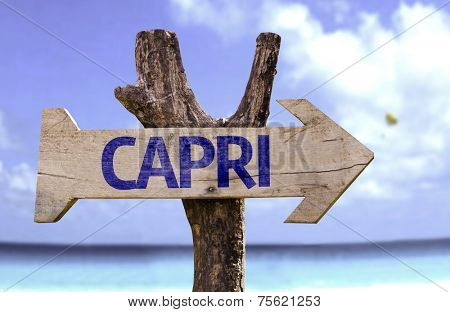 Capri wooden sign with a beach on background