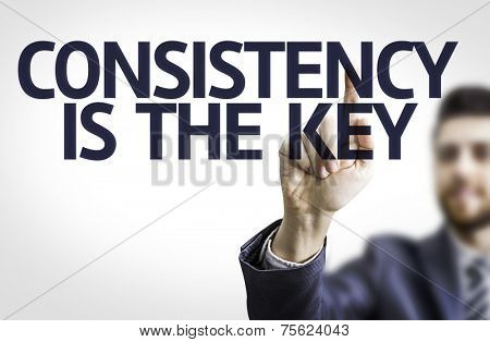 Business man pointing to transparent board with text: Consistency is The Key