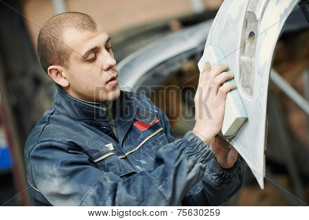 auto mechanic worker sanding polishing bumper car at automobile repair and renew service station shop by sandpaper