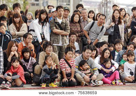 OSAKA, JAPAN, NOVEMBER 13, 2011: Japanese public crowd is watching a magician show performed at the aquarium square in Osaka, Japan