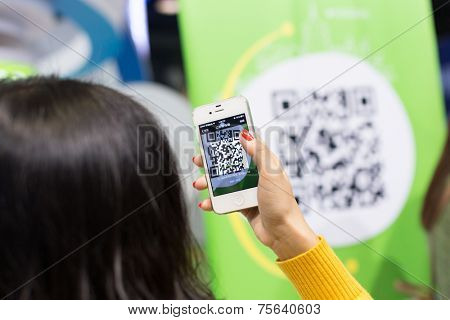Hangzhou,China-1,11,2014:chines young woman scan the QR code with smart phone.