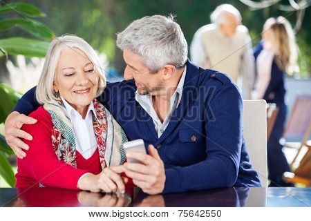 Affectionate grandson and grandmother using smartphone with family in background at nursing home