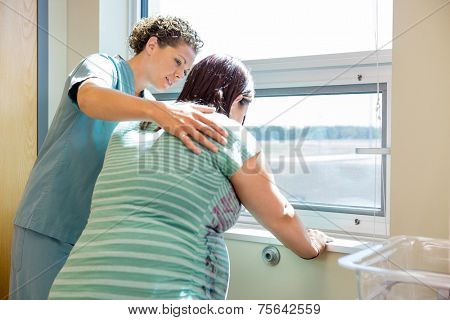 Mid adult female nurse comforting tensed pregnant woman leaning on window sill in hospital room