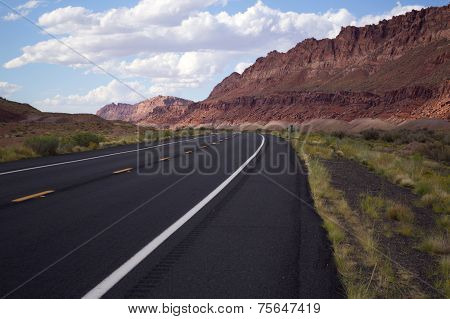 Empty Road Leading Off Into The Beautiful, Red Mountains Of Norther Arizona