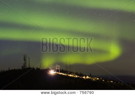 Aurora Borealis Over Hill With Antennas And Car With Lights On