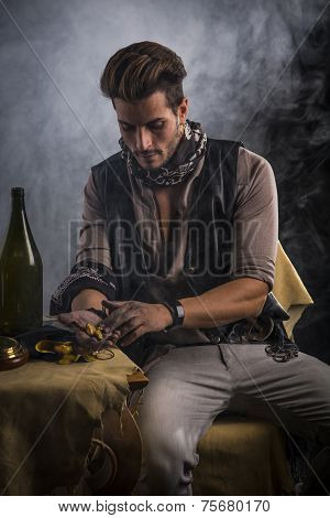 Young Man In Pirate Fashion Outfit Looking At Gold In Hand