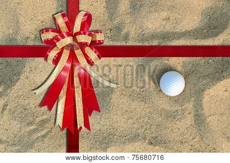 Red Ribbon On A Golf Ball On The Sand For Background