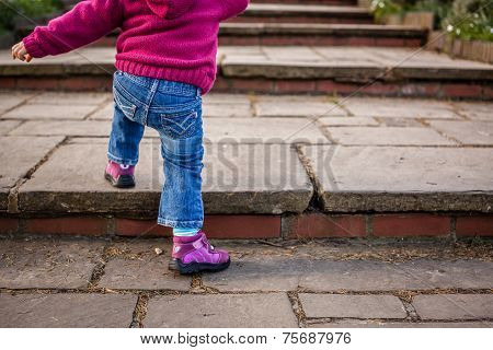 Baby girl climbing steps