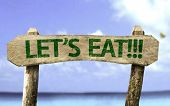 Let's Eat!! wooden sign with a beach on background poster