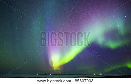 Curving Aurora borealis over rural landscape