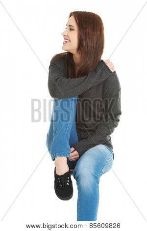 Sitting young happy woman holding a leg
