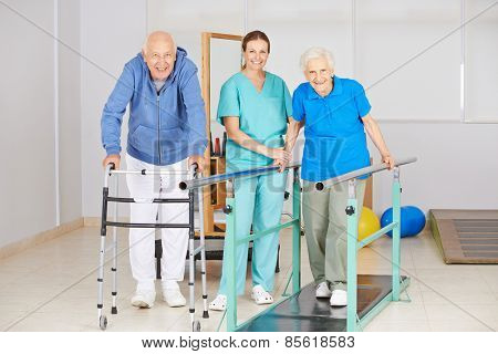 Two senior people doing walking exercise in physiotherapy with physiotherapist