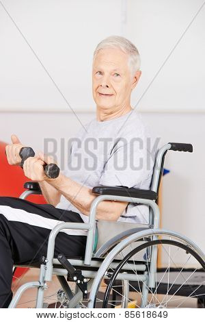 Older man in wheelchair in physiotherapy training with dumbbells