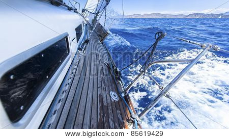 Sailing. Racing yacht in the Mediterranean sea on blue sky background. Luxury Lifestyle.