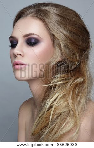 Portrait of young beautiful blonde girl with stylish messy hairdo and smoky eyes make-up