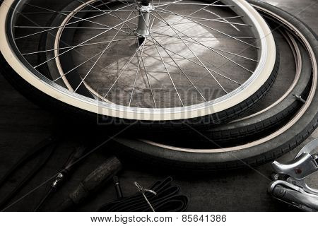 Bicycle repair in monotone. Repairing or changing a tire, tire tubes and brakes wires of an vintage bicycle.