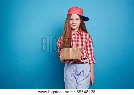 Little girl holding a box, tied with ribbon