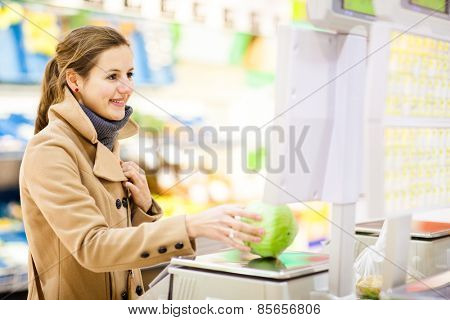 Beautiful young woman shopping for fruits and vegetables in produce department of a grocery store/supermarket (shallow DOF; color toned image) poster