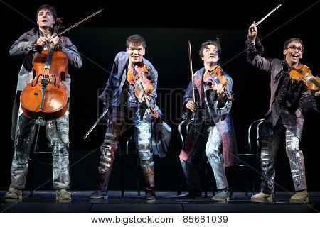 MOSCOW - MAR 12, 2014: Four cheerful men Taper-show: dancing on the strings in costumes with musical instruments on stage of the Palace on Yauza