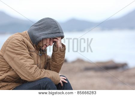 Worried Teenager Guy On The Beach In Winter