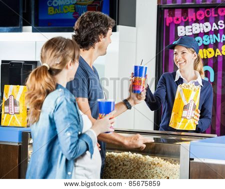 Happy female seller selling popcorn and drinks to expectant couple at cinema concession stand