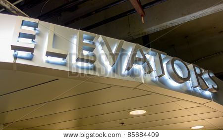 a lit elevator sign of aluminum letters poster