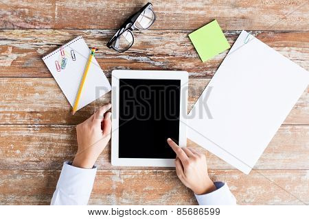 business, education, people and technology concept - close up of female hands pointing finger to tablet pc computer black blank screen with paper, notebook and eyeglasses
