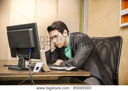 Preoccupied, Worried Young Male Worker Staring At Computer