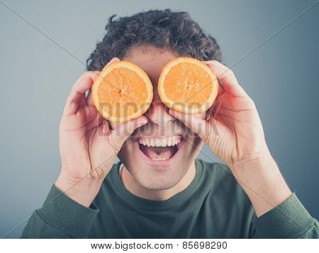 Silly Young Man Using Oranges As Binoculars