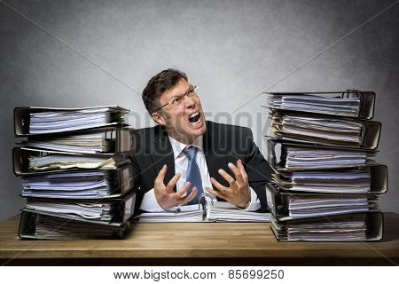 Overworked crying businessman with lot of files on his desk poster