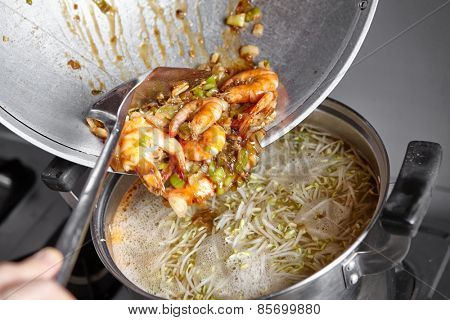 Adding the stir fried shrimp with leek and garlic to the soup