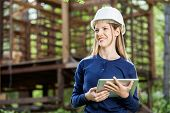 Happy female architect holding digital tablet against incomplete timber cabin at construction site poster