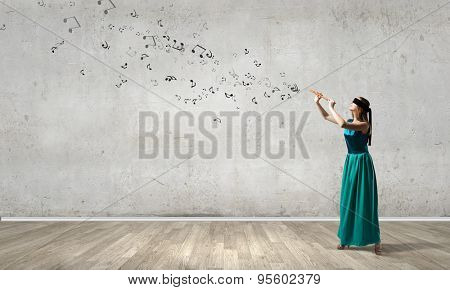 Young pretty woman in green long gress playing fife