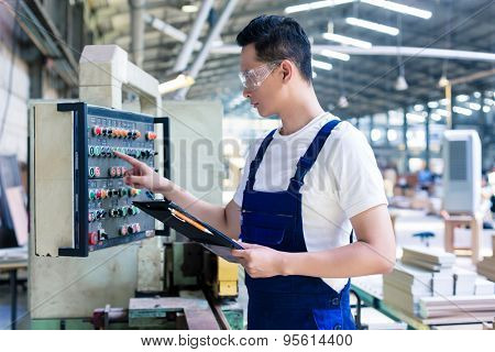 Worker pressing buttons on CNC machine control board in Asian factory