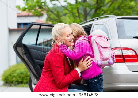 Mother consoling daughter on first day at school, the kid being a bit afraid of what may lay ahead