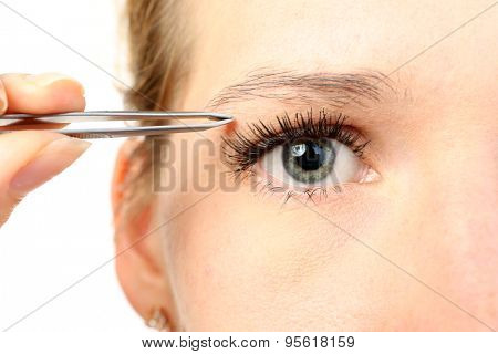 Young woman plucking eyebrows with tweezers close up poster