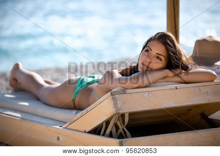 Relaxed beautiful woman sunbathing in a bikini on a beach at tropical travel resort,enjoying summer