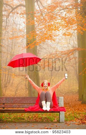 Girl In Autumn Park Enjoying Hot Drink