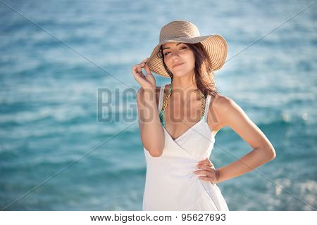 Beautiful woman in a white dress walking on the beach.Relaxed woman breathing fresh air