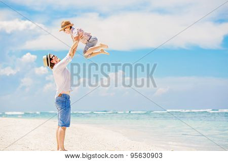 Young happy father playing with his little son standing barefoot at the beach with ocean and beautiful clouds on background. Having fun with the kid in summer coast on holidays poster