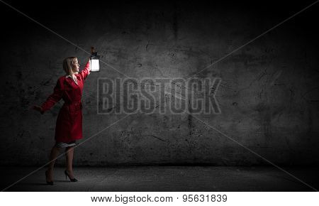 Young blond woman in red cloak with lantern lost in darkness