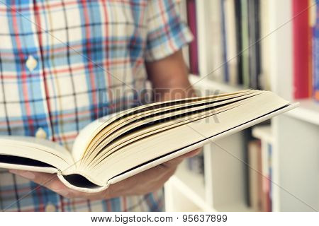closeup of a young caucasian man reading a book in a library