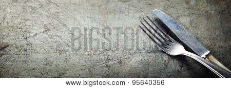 Dining fork and knife on rustic vintage background with copyspace
