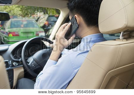 Man Driving His Car While Talking On The Phone