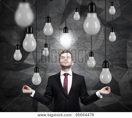 Meditating Businessman Is Searching New Ideas. Lots Of Light Bulbs. Dark Contemporary Background.