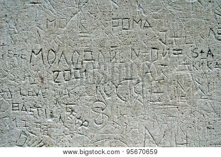 Close-up carved names on stone wall