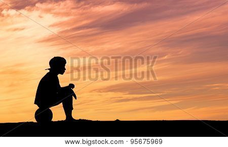 Silhouette of a boy sitting on football or soccer ball at the beach with sunset background